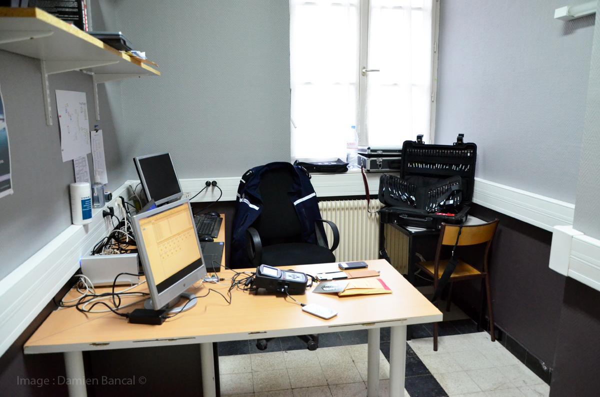 Un bureau, des ordinateurs et une valise capable de lire l'ensemble des téléphones portables du marché.